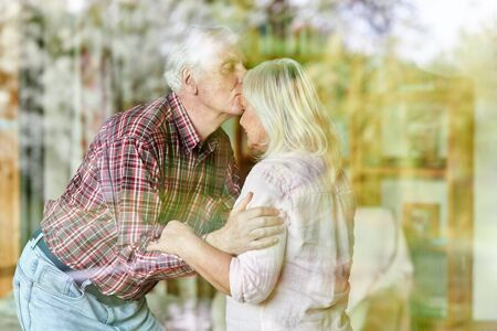 Senior gives his wife a kiss on the forehead as a sign of love and closeness Archivio Fotografico - 150512860