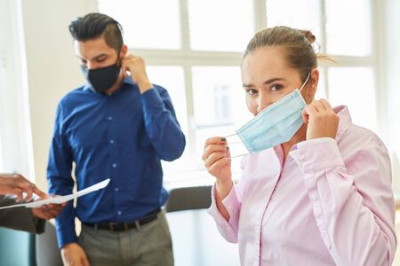 Two businesspeople with mouth and nose protection in the office because of Covid-19 and coronavirus pandemic