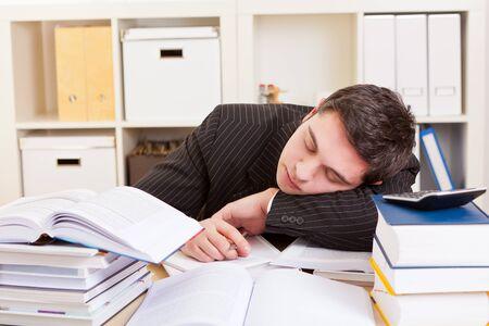 Businessman falls asleep at desk over many books Archivio Fotografico - 150512831