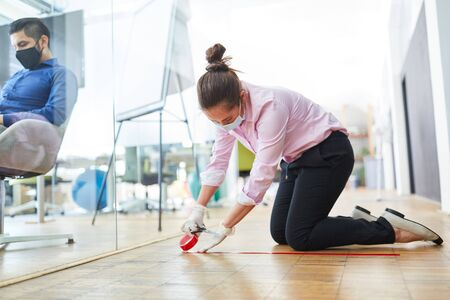 Businesswoman marks floor in office with tape as prevention against Covid-19 and Coronavirus