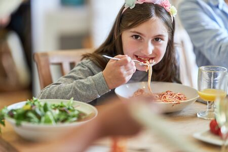 Happy girl is eating spaghetti with tomato sauce at home with the family