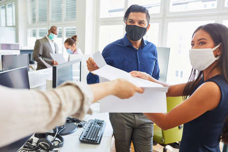 Start-up business people with face mask because of Covid-19 get an important document Stock Photo