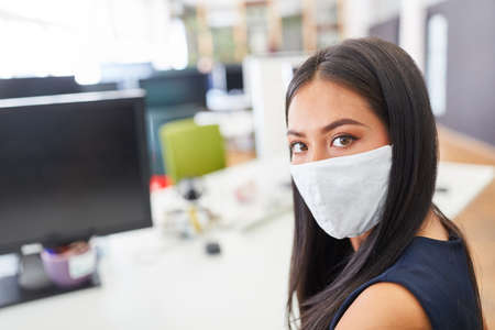 Young business woman in start-up office with face mask because of Covid-19 and coronavirus pandemic