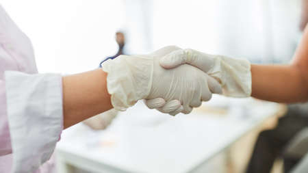 Business people handshaking with rubber gloves as a prevention against Covid-19 and corona virus 免版税图像