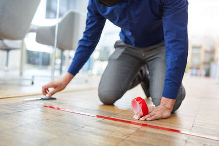 Business man marks floor in office with tape as measure against infection with Covid-19