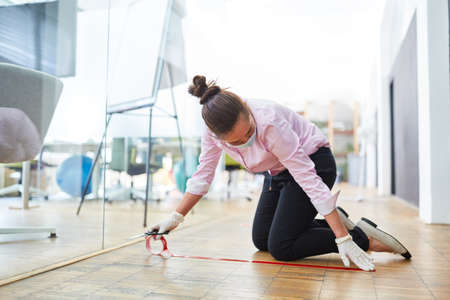 Businesswoman marks floor in office with tape for keeping distance as prevention against Covid-19 Stockfoto