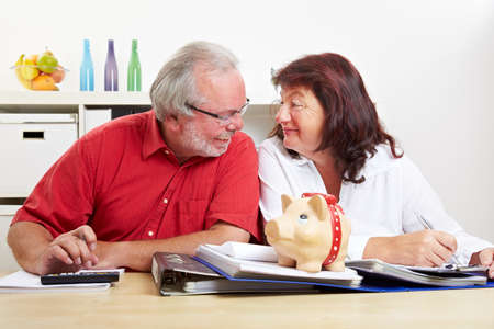 Senior couple doing financial planning at desk with piggy bank and calculator Stock fotó - 151488651
