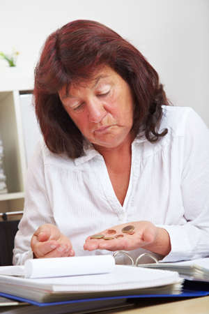 Elderly woman looks at euro coins in her hand Stock fotó