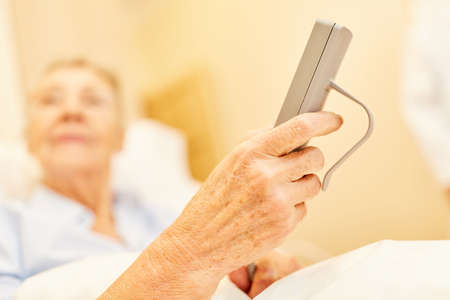 The patient is lying in bed holding the remote control from the nursing home care bed