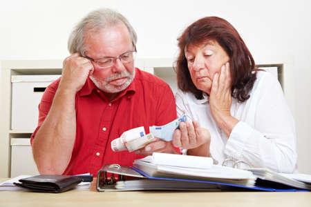 Two worried seniors count euro bills at their desks