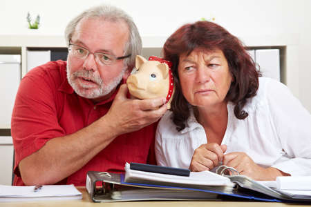 Seniors are listening to an empty piggy bank at the desk Stock fotó - 151488729