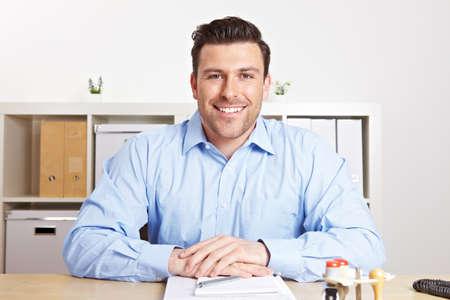 Smiling HR representative in office talking at desk