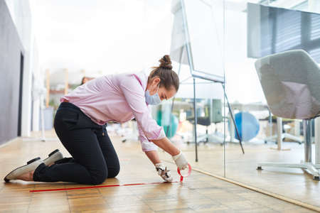 Woman marks floor with tape for keeping distance in business office because of Covid-19 and Corona virus