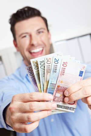 Laughing winner with fan of money from euro bills