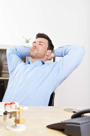 Relaxed manager in the office leans back at the desk