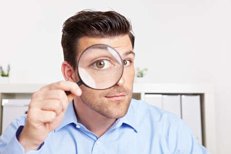 Attractive manager in the office looks through a magnifying glass with his eye