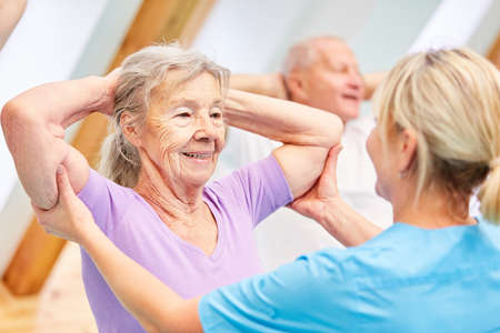 Trainer helps seniors with healthy back training in physiotherapy Stock Photo
