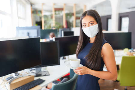 Businesswoman in open-plan office with mouth and nose protection for Covid-19 and coronavirus Stock fotó - 151416813