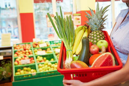 Woman holding a basket filled with fruits and vegetables in supermarket