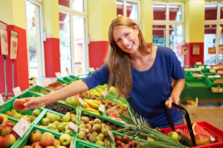 Laughing young woman reaches for fruit in the supermarket