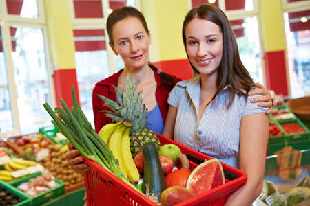 Mother and daughter with full shopping basket in the supermarket Standard-Bild