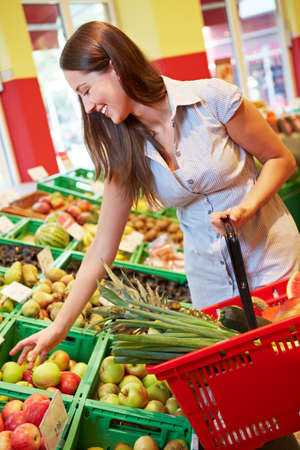 Young smiling woman buys fruit in the supermarket