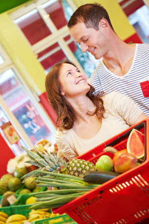 Smiling couple with fruit in shopping basket in supermarket Standard-Bild