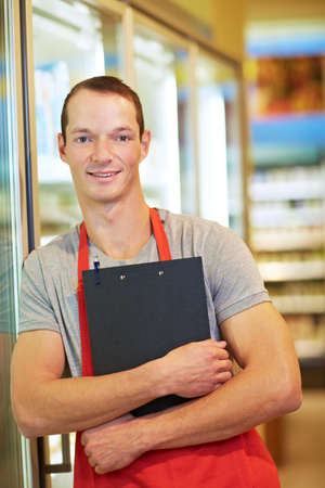 Retail salesman stands with clipboard leaning against chilled shelf in supermarket Reklamní fotografie