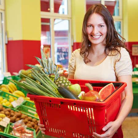 Smiling brunette woman carries a shopping basket in the supermarket Standard-Bild