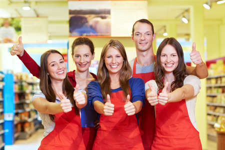 Successful laughing supermarket team holds all thumbs up 免版税图像