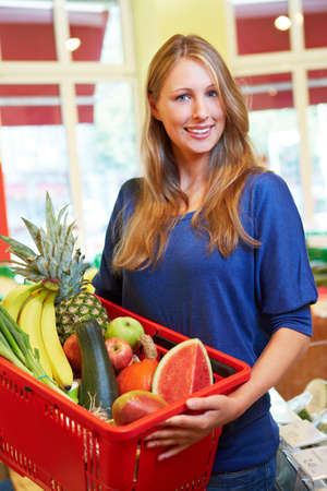 Smiling young woman with full shopping basket in supermarket