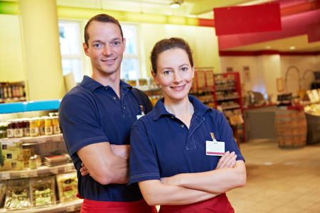Store manager and employee stand smiling with crossed arms in the supermarket