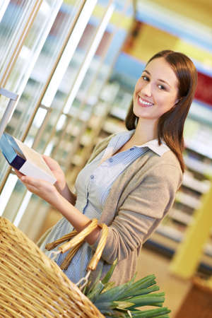 Young woman with shopping basket buys frozen goods in the supermarket Stock Photo