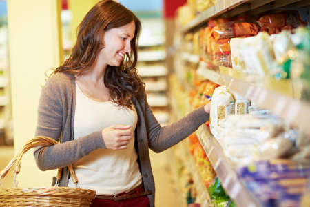 Woman with shopping basket is standing on the shelf in the supermarket