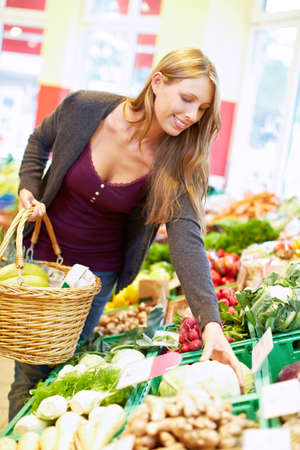 Young attractive woman buys her vegetables in the organic market Standard-Bild