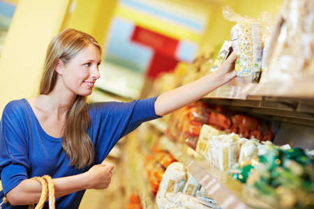 Attractive woman with shopping basket reaches for pasta in supermarket Standard-Bild - 151417263