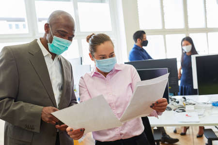 Two businessmen with face mask over Covid-19 talk about a business document in the office