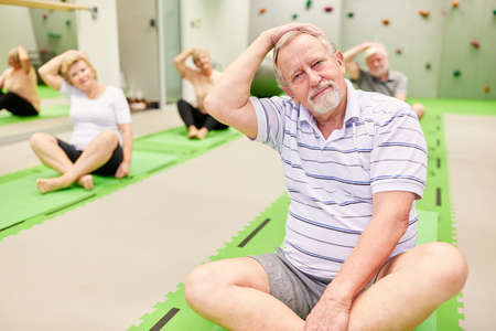 Group of seniors doing sports at back gymnastics class in Pilates studio