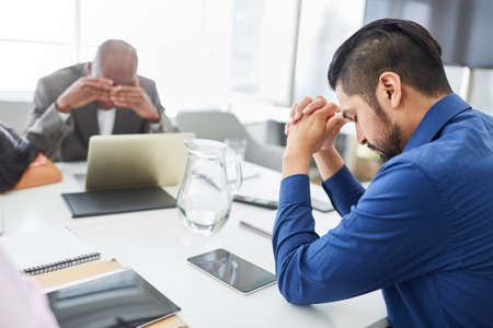 Desperate and sad business people sitting at conference table after bankruptcy or layoff Banque d'images - 151489380