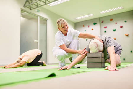 Trainer or physiotherapist cares for seniors during back training with the yoga block