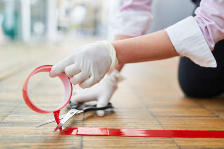 Business woman marks floor with red tape as an indication to keep distance because of Covid-19
