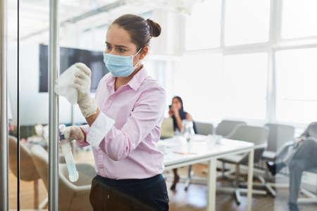 Cleaning lady with face mask because of Covid-19 when disinfecting in the office with disinfectant