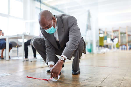 African businessman marks office floor with tape for distance because of Covid-19