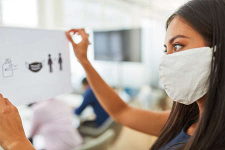 Businesswoman with mask because of Covid-19 fastens a notice board with hygiene rules in the office