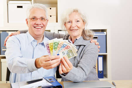A smiling couple of seniors holds up a fan of euro bills Stock fotó