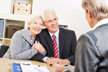 Smiling couple of seniors in counseling session with a client advisor