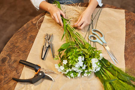 Hands of a florist in flowers tying with bast for a bouquet Stock Photo
