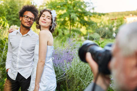 Photographer takes pictures of happy newlyweds on wedding day in nature