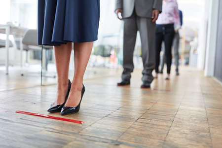 Employees keep a distance of two meters in the office using distance marking because of Covid-19