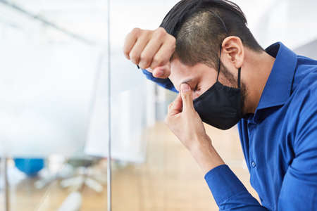 Business man with face mask because of Covid-19 in the office suffers from overload or burnout Banque d'images - 151492642